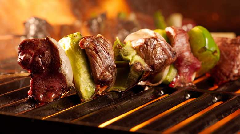 Griiled meat on skewers over flame