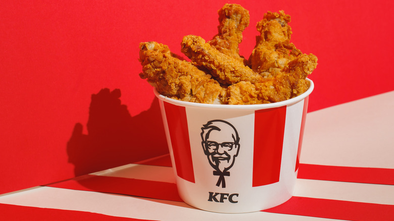 Bucket of KFC fried chicken against red wall