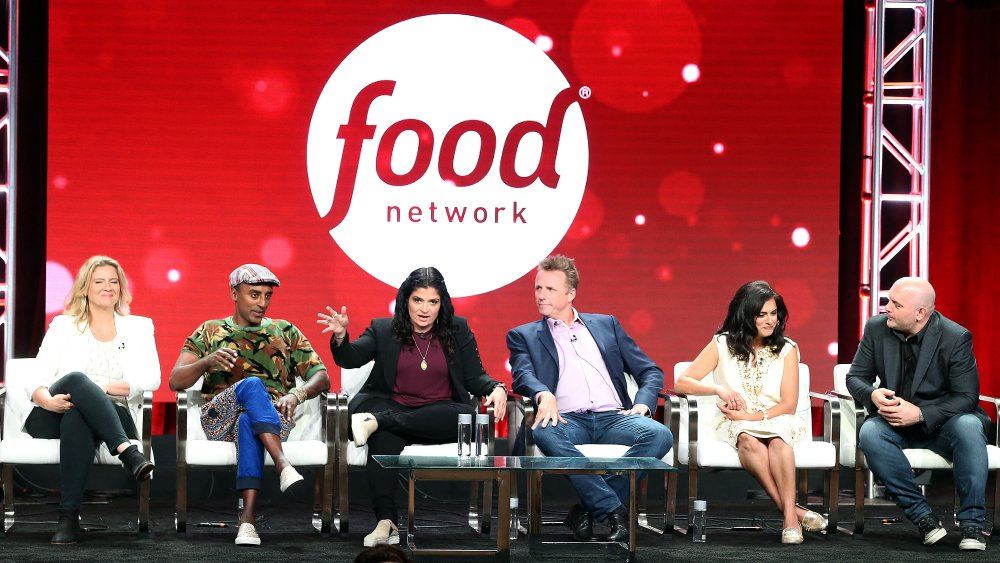 The Chopped cast sits in front of a Food Network sign