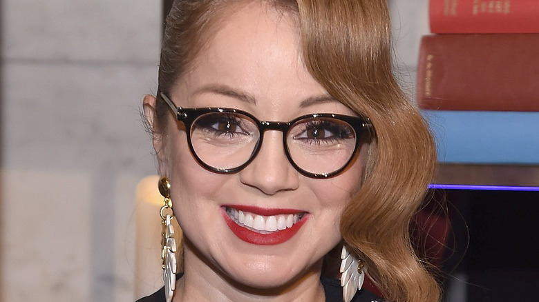 Marcela Valladolid wearing red lipstick smiling.