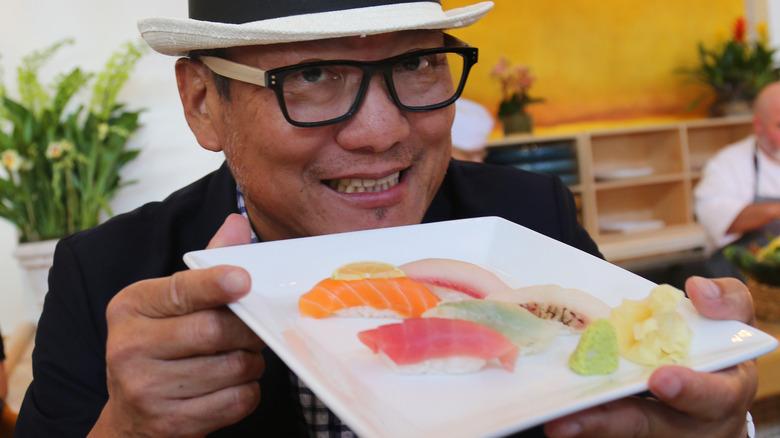 Chef Morimoto holding up a plate of nigiri sushi