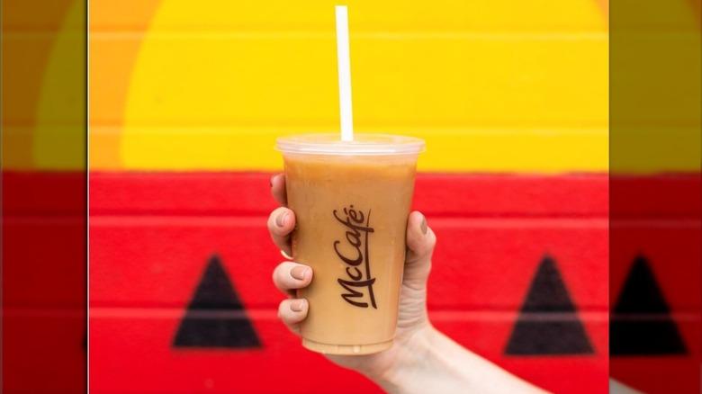 Hand holding McDonald's iced coffee