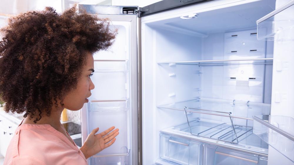 Woman staring into empty refrigerator