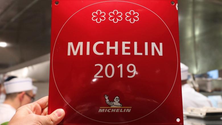 Person holding Michelin Star plaque
