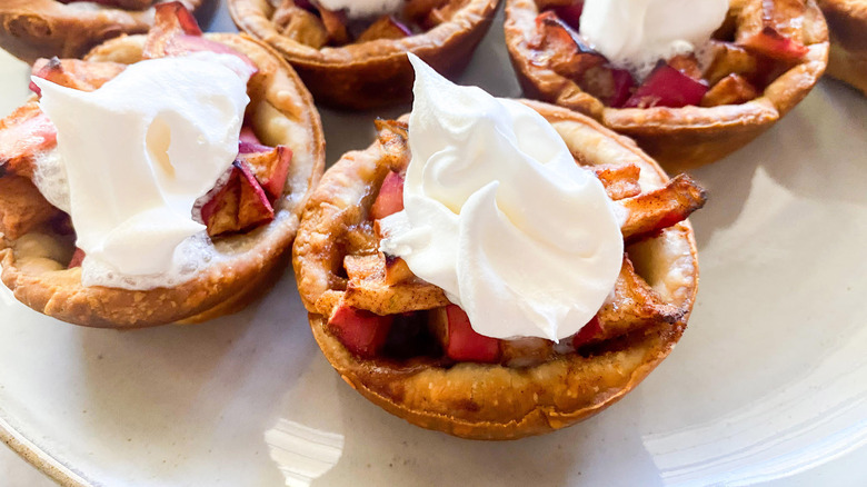mini apple pies with whipped cream topping on white plate