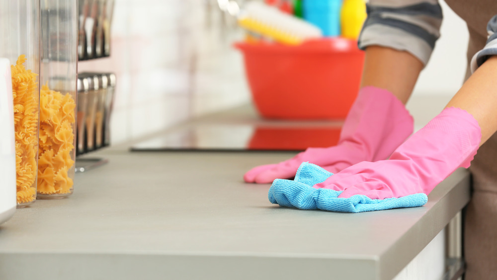 person cleaning kitchen countertop with cloth