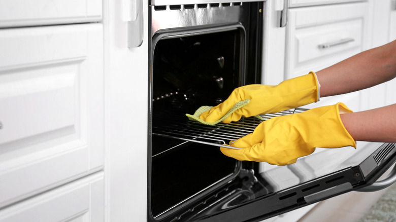 Hands wearing rubber gloves while cleaning an oven