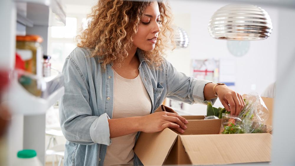 woman unpacking groceries in refrigerator
