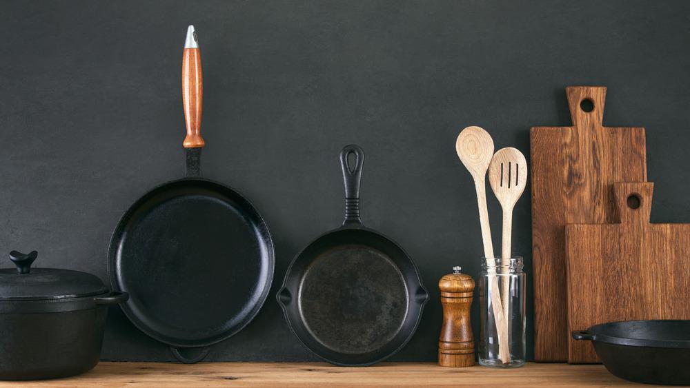 Cast iron skillets alongside a Dutch oven