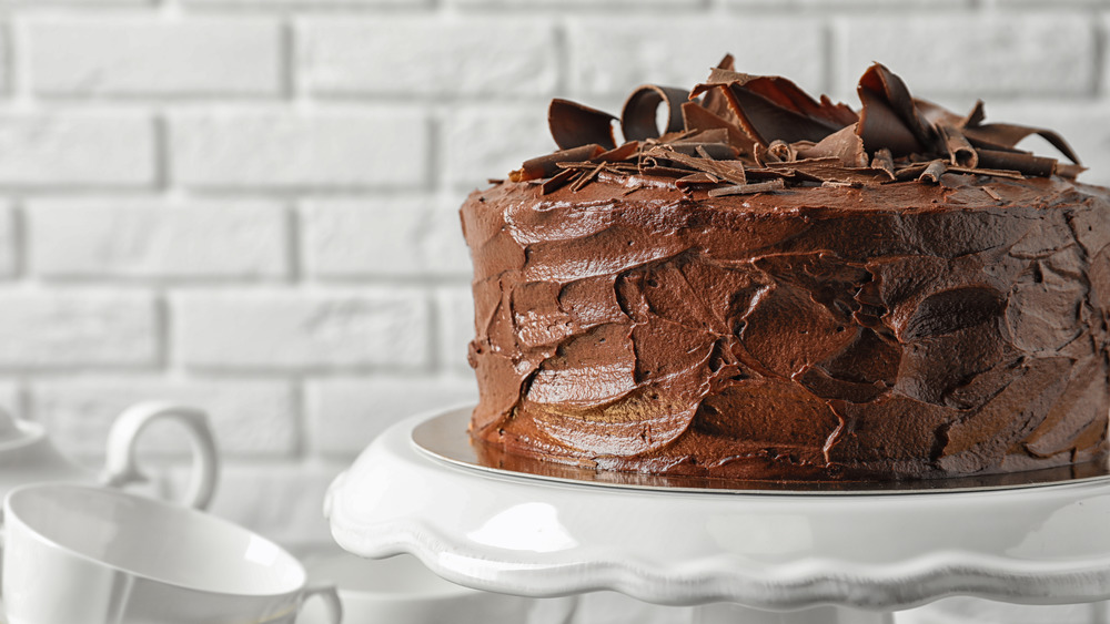 chocolate frosted cake on pedestal