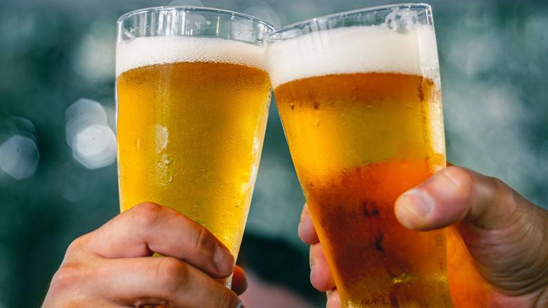 Two pints of beer being cheersed