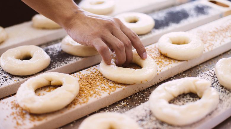 Person making bagels with seasonings