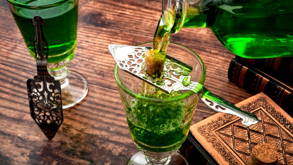 Absinthe being poured over a sugar cube into a glass