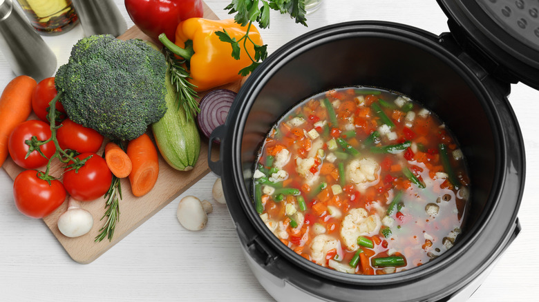 Vegetables on cutting board and in slow cooker
