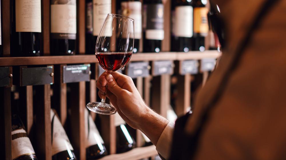 Person holding wine glass in wine cellar