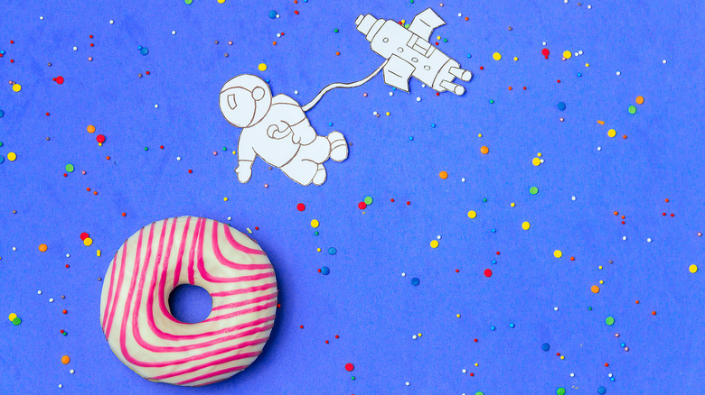 Cartoon astronaut approaching frosted donut
