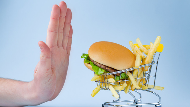 Burger and fries in shopping cart being pushed away by hand