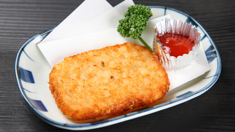 A hash brown patty on a plate with ketchup