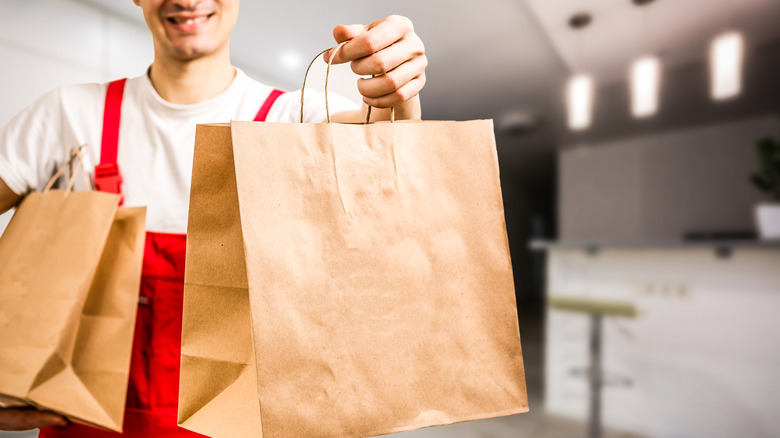 fast food worker holding bags out to customer