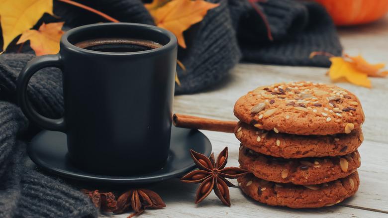 Pumpkin spice cookies alongside black mug with cinnamon