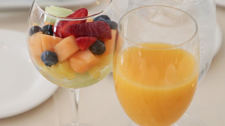 Glass of orange juice next to fruit