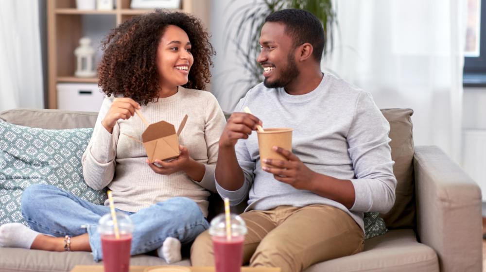 A couple enjoys their restaurant food at home on the sofa