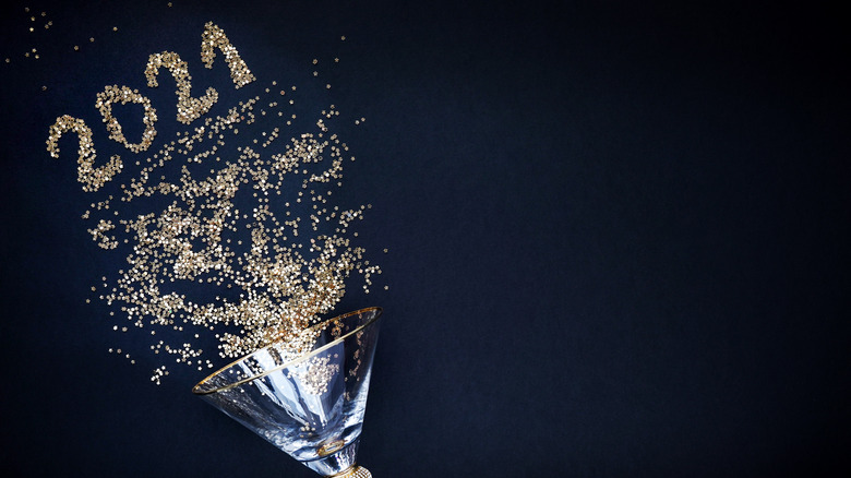 Martini glass and 2021 in gold glitter stars on black background