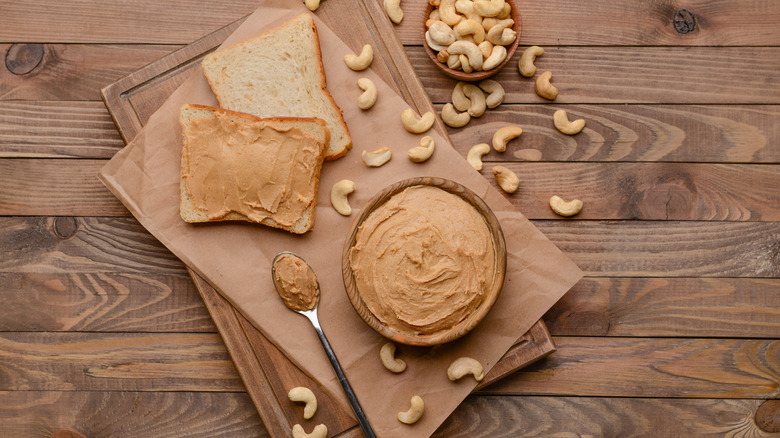 Cashew butter on a wooden table with sliced bread