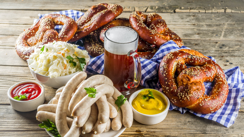 Sausages, pretzels, and beer on wooden surface