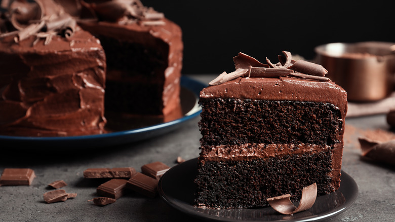 Whole chocolate cake with slice on plate