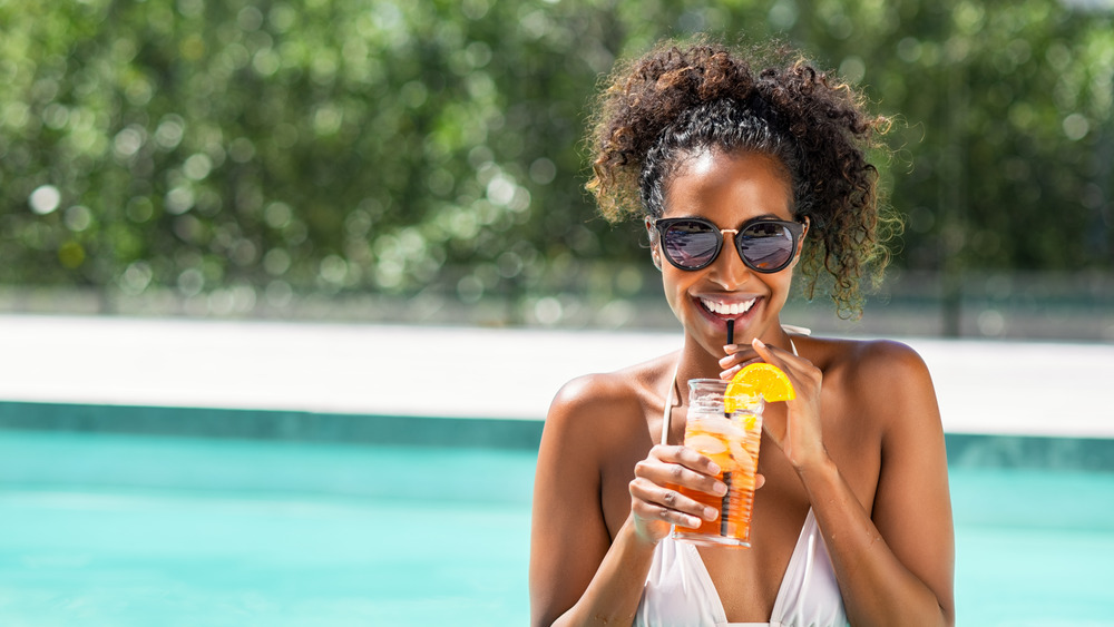 Woman in swimming pool with drink