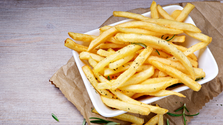 Seasoned French fries on wood table
