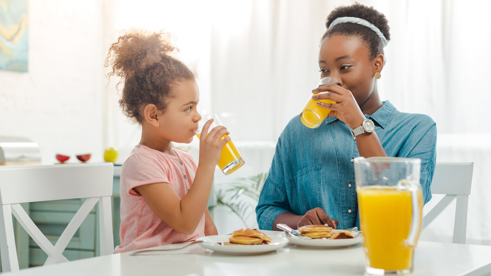 Mom and daughter drinking orange juice