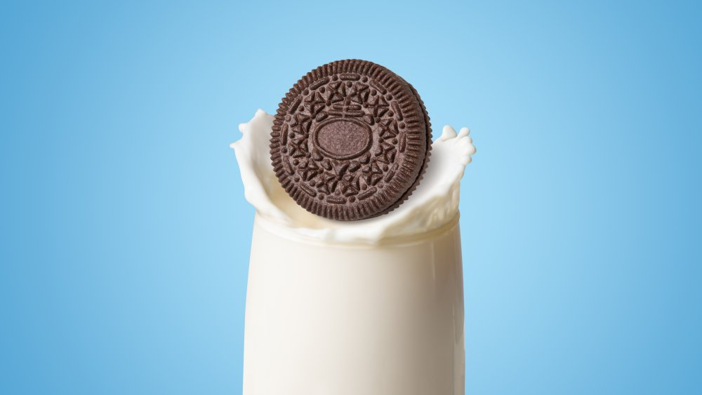 Oreo falling into a glass of milk