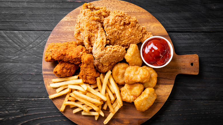 A tray with fried chicken, chicken strips, chicken nuggets, French fries and a container of ketchup.