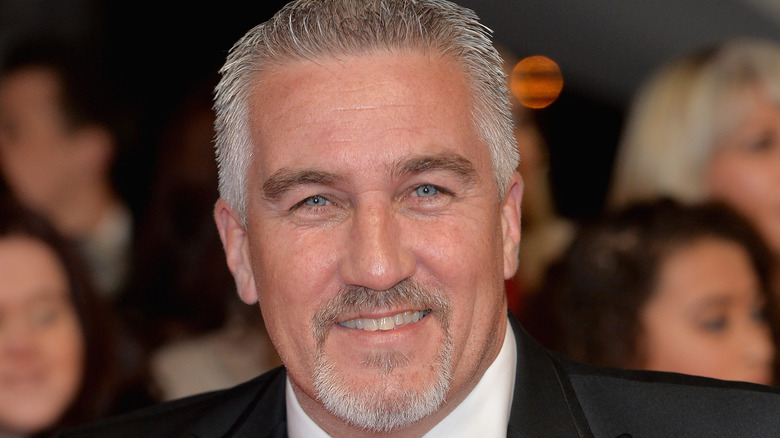 Paul Hollywood smiling wearing a black suit