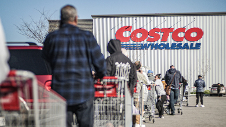 People with shopping carts waiting in line for Costco