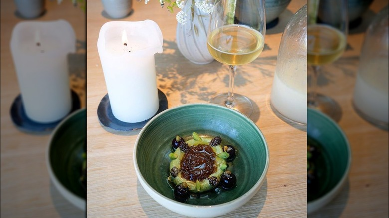 Candied pine cones at Noma next to candles and wine