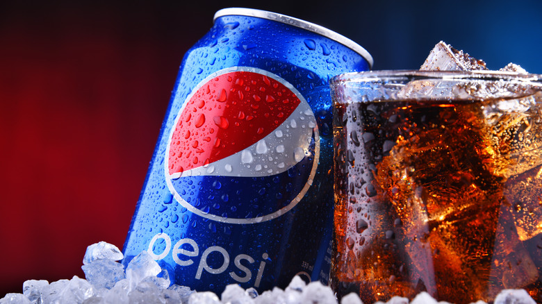 A can of Pepsi sitting next to a glass