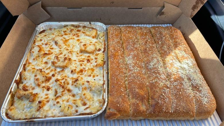 A tray of Pizza Hut's Creamy Alfredo Pasta and breadsticks.