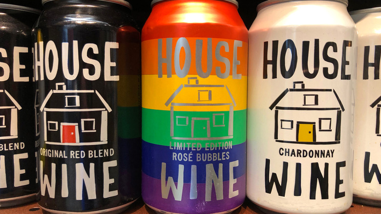 Grocery store shelf with cans of HOUSE brand Wines. Red, rose bubbles and chardonnay