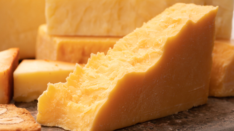 A block of yellow cheddar cheese