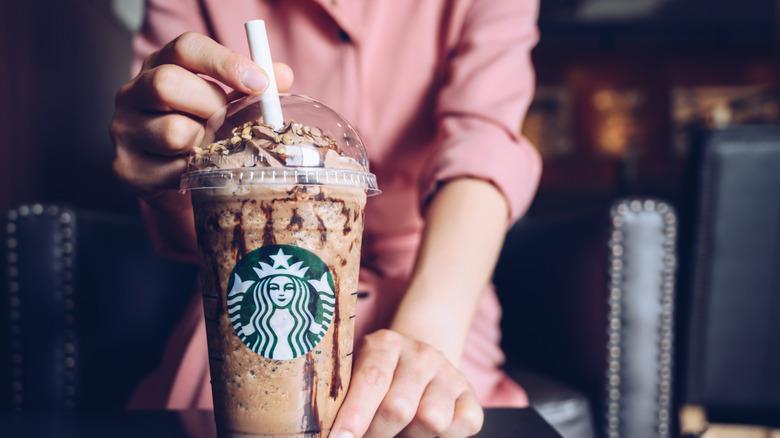 A person holding a Frappuccino