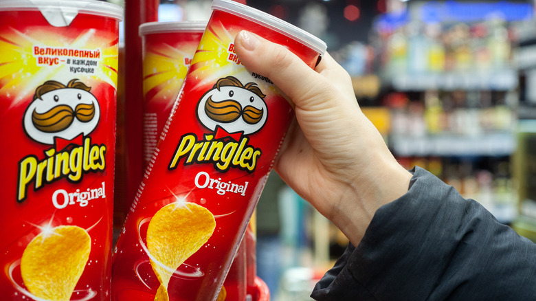 Person grabbing a can of potato chips