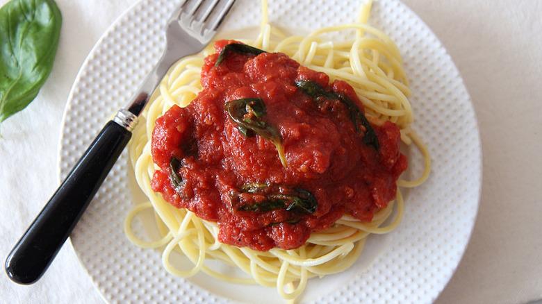 marinara sauce with spaghetti on white plate