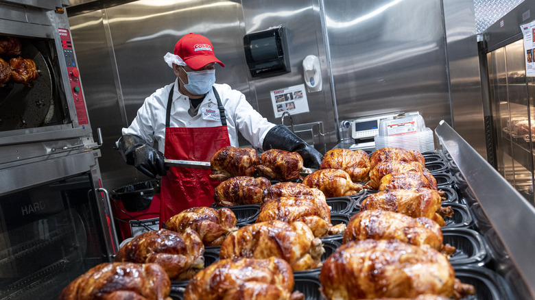 Worker with rotisserie chickens