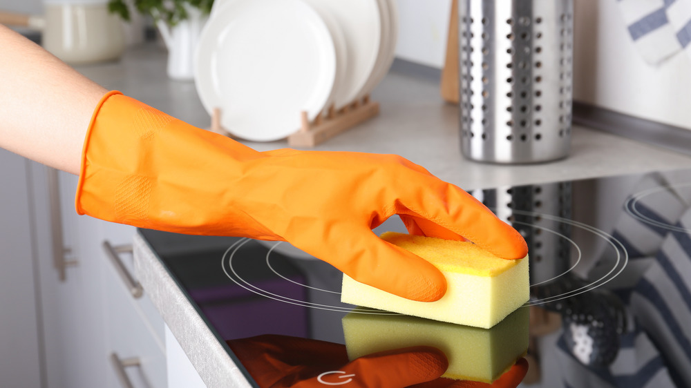 Gloved hand cleaning stovetop