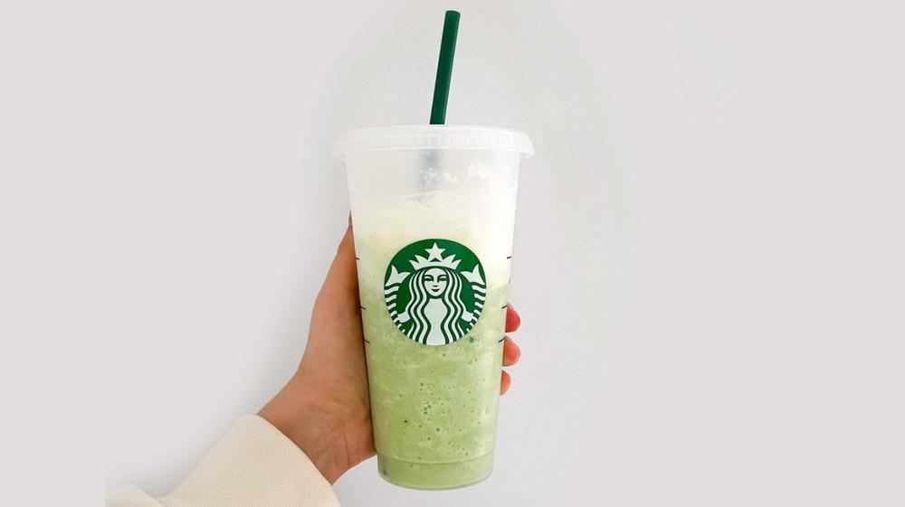 Woman holding an iced matcha latte