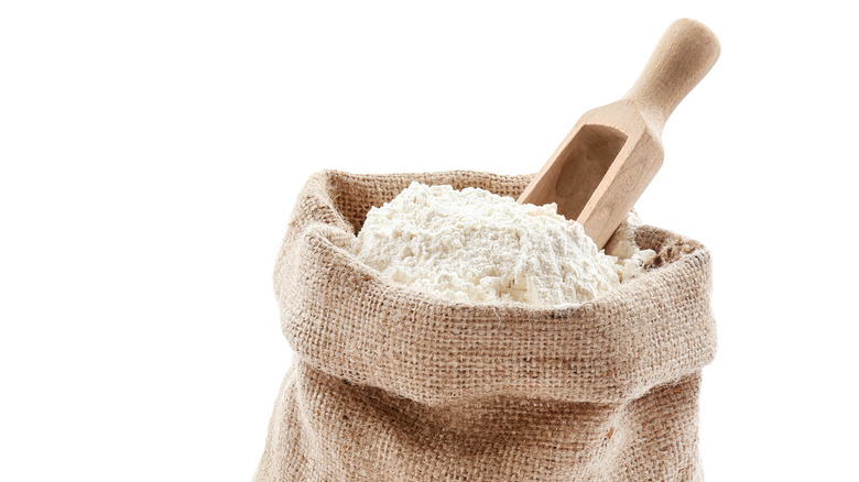Burlap sack of flour with a wooden scoop