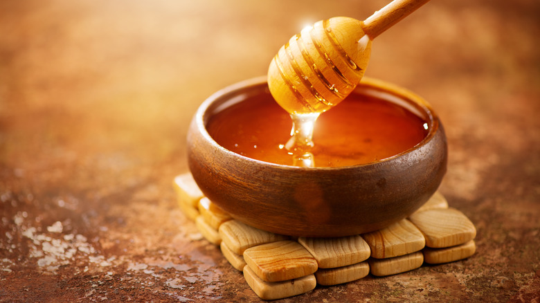 honey and dripper with wooden bowl